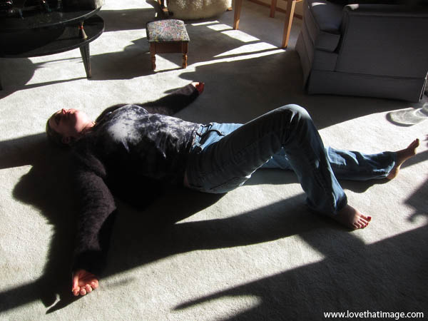 woman supine, woman in jeans on carpet, sunshine and shadows indoors
