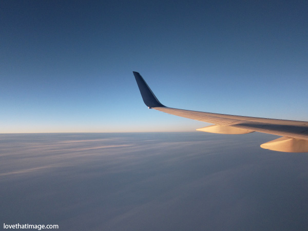 airplane wing over cloud cover at sunset, deep blue sky from above the clouds