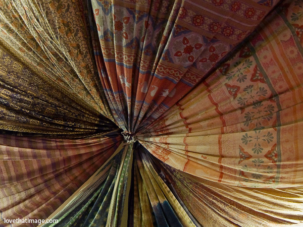 central radius image, gathered fabric, tan, red and green patterened fabric, ceiling fabric, cloth
