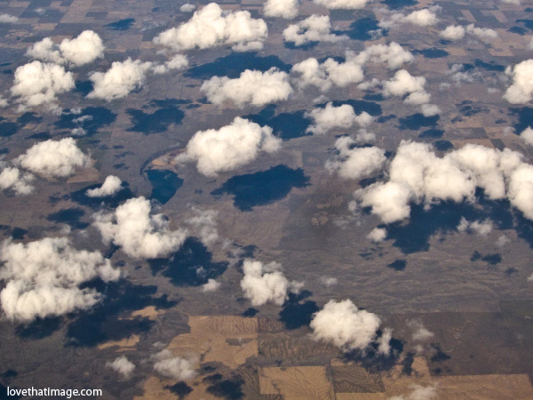 puffy clouds from above, midwest from air, fields in late winter, white clouds with shadows