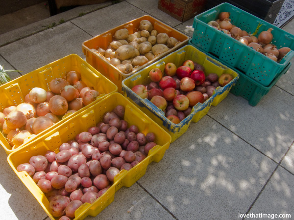 bins of produce, farmers market, bright plastic bins, colorful, round, apples, red potatoes,  onions