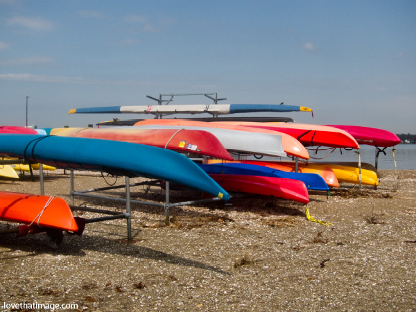 kayak shells on the beach, boats stacked for winter, colorful boats, boat hulls