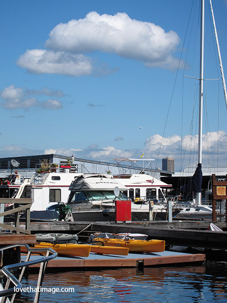 Lake Union, seattle, puffy clouds, boats, mast, yellow kayaks