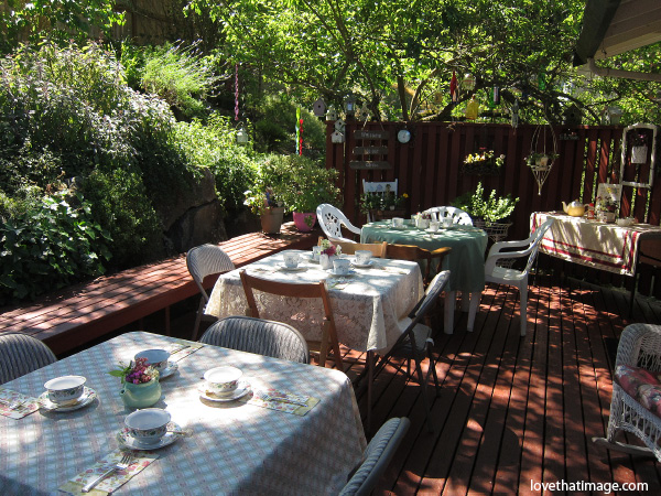 tea party in the garden, dappled sunshine on deck,woodsy party setting