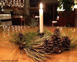 pine needles, centerpiece, lit candle, fireplace, warm holiday scene