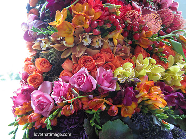 rainbow bouquet, pink roses, orange roses, orange freesias, yellow orchids