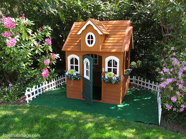 Playhouse with a picket fence nestles among the rhododendrons