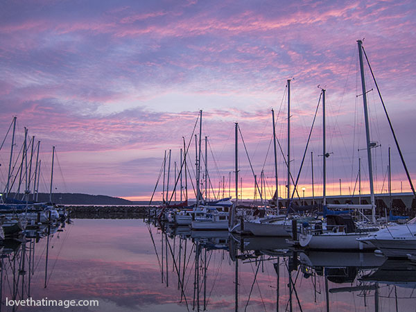 Colorful sunset at Des Moines WA marina with boats and water reflections