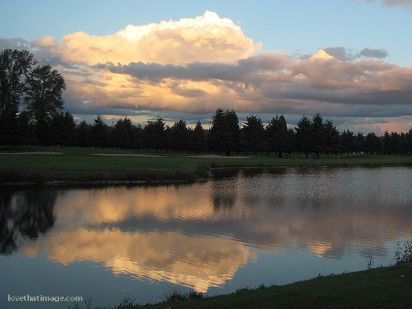 Clouds at dusk reflected in a golf course pond
