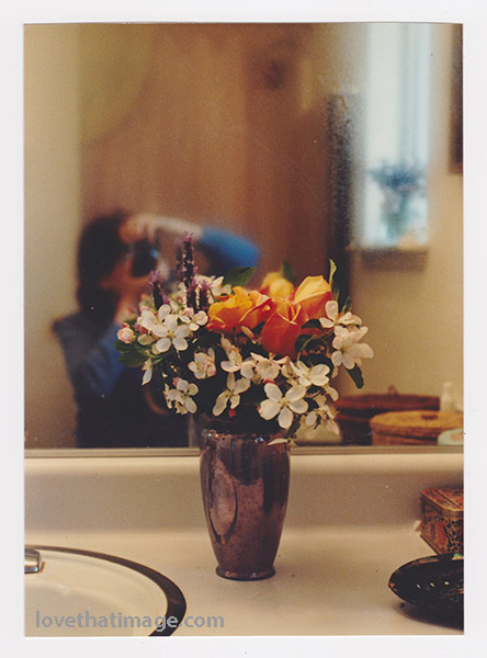 Roses and white flowers in a bouquet, with the photographer reflected in the background