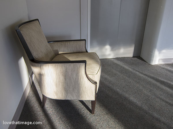 Beige armchair in late afternoon light, near an elevator