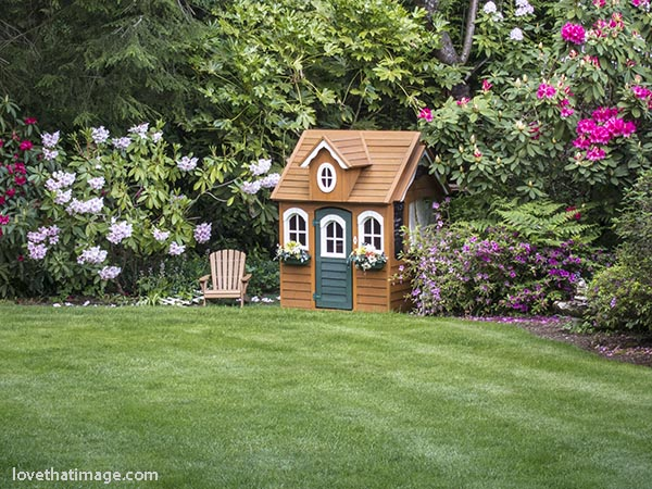 Backyard playhouse complete with kid-sized adirondack chair and rhodies blooming
