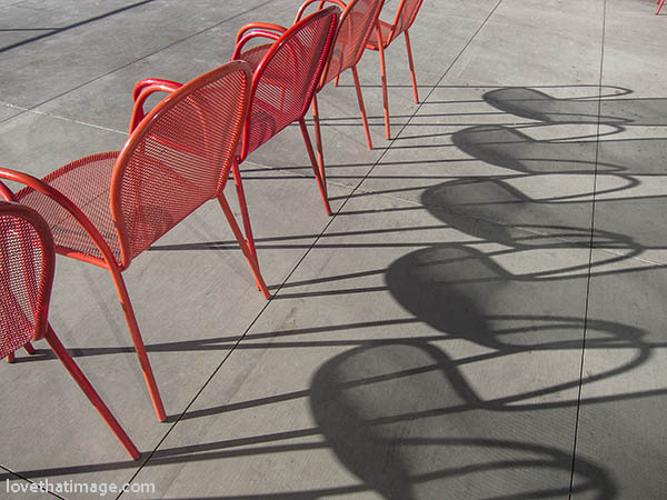 Tomato red metal chairs casting fine shadows on the big patio at the Olympic Sculpture Park in Seattle