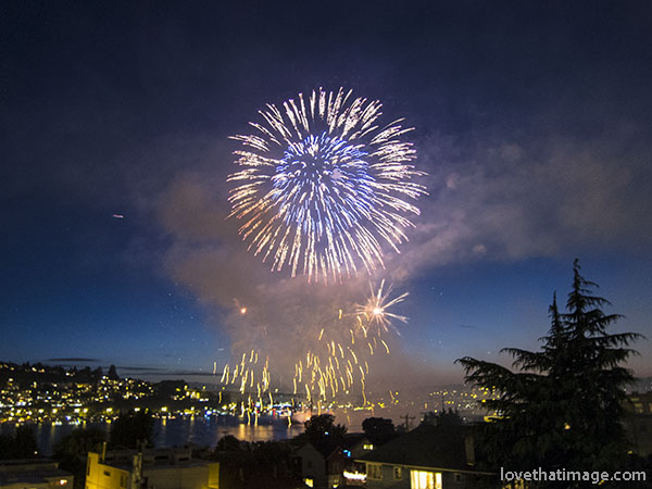 Fireworks explode over Lake Union in Seattle at dusk on July 4.