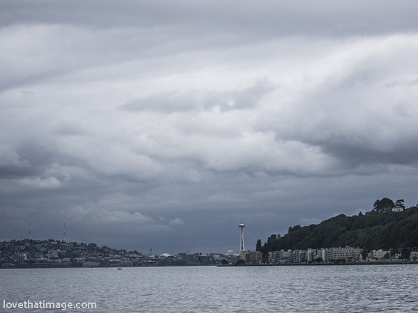 Looking north to Seattle's Space Needle, from Alki Beach, under dramatic gray skies