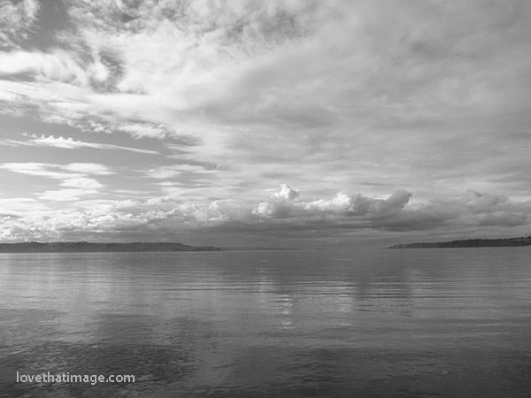 Monochromatic photo of dramatic sky and calm Puget Sound in the Pacific Northwest