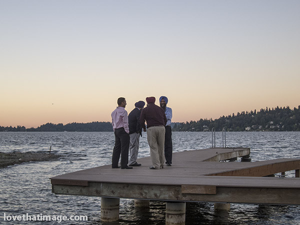 Indian men standing on a pier at Lake Washington in Seattle, at sunset