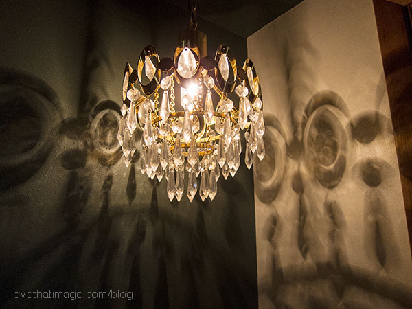 Small crystal and gold chandelier casts shadows on the wall at night