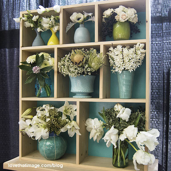 Several bouquets in pale tones and shades of turquoise decorate a bookcase