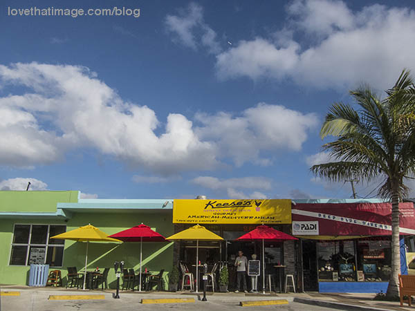 Red and yellow umbrellas, green building and bright blue skies in Southern Florida
