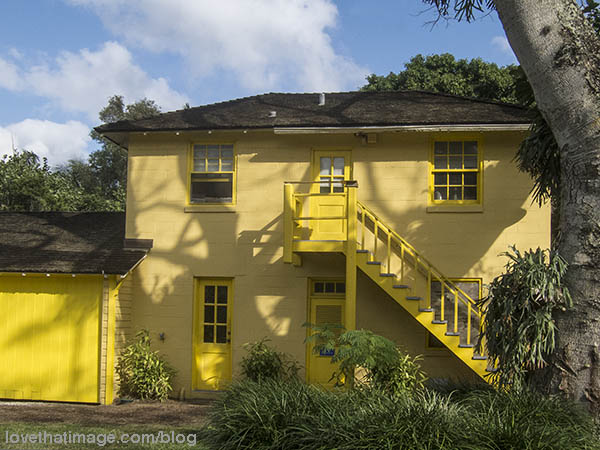 At the Bonnet House and Gardens, a yellow house with a brighter yellow staircase outside.