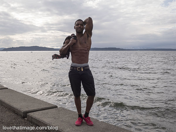 Well-muscled young man in red shoes at the edge of Puget Sound in Seattle, WA
