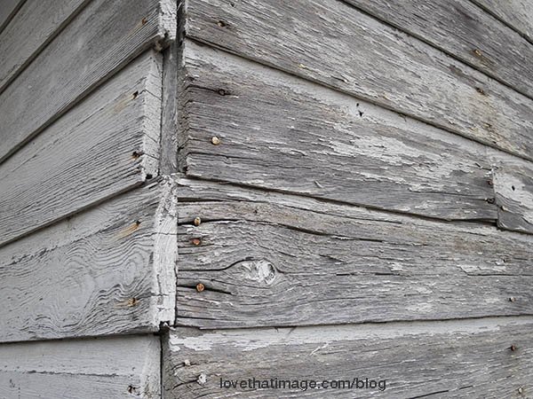 Antique building needing paint, with wooden siding
