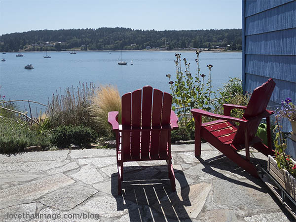 Red adirondak chairs look out over Poulsbo Bay