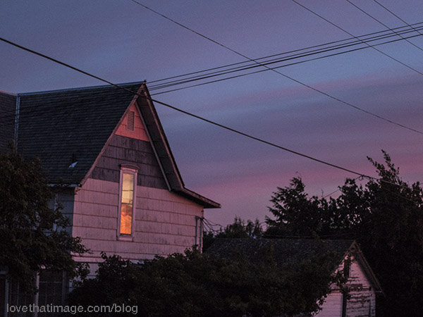 Sunset reflected in an old cottage window in Port Townsend, WA