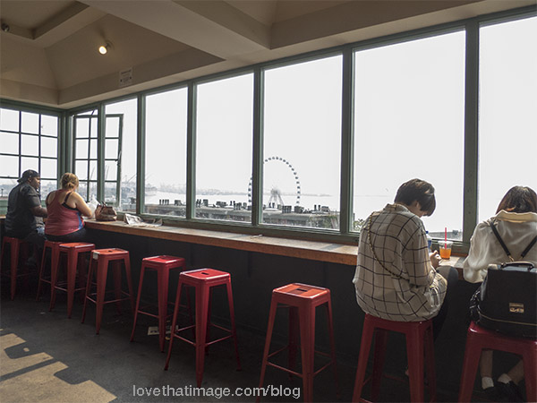People sit at a counter with a view of the smoky skies and the Great Wheel in Seattle