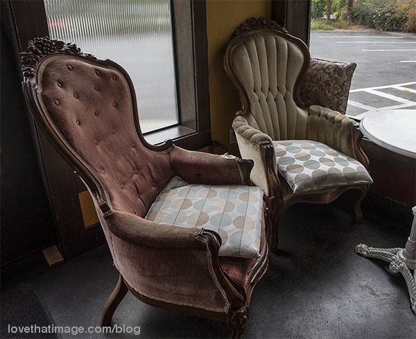Old upholstered chairs with carved wood and tufted backs still have some faded glory.