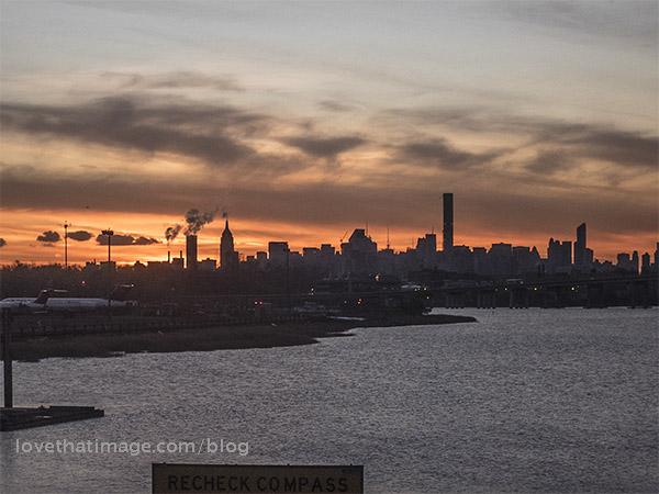 Empire State Building visible in the New York City skyline at sunset, from LaGuardia Airport