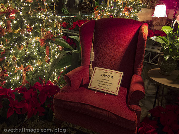 Red chair next to electric train and Christmas tree, decorated with lights and bows