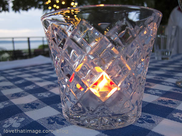 Candle in a cut-glass holder at the shore of Puget Sound on a summer evening