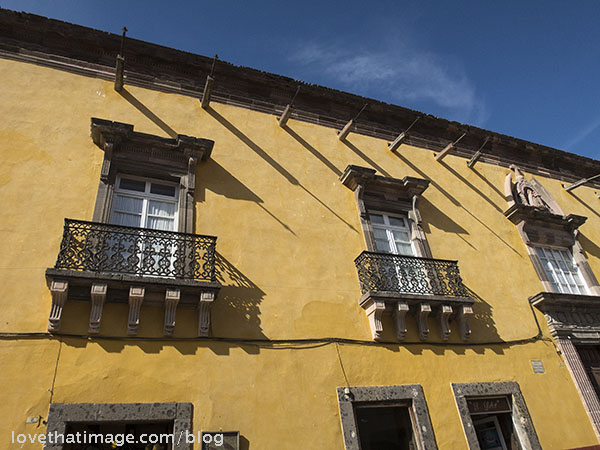 Ochre yellow walls and wrought iron window railings in El Centro (downtown) in San Miguel in Mexico