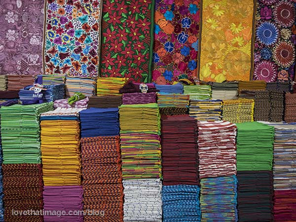Stacks of neatly folded, colorful fabric on display in San Miguel de Allende, Mexico