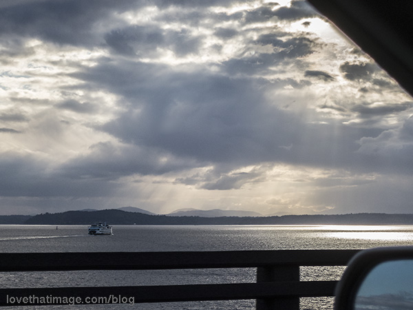 Ferry in Puget Sound heading out of Seattle,  into dramatic sky vista.