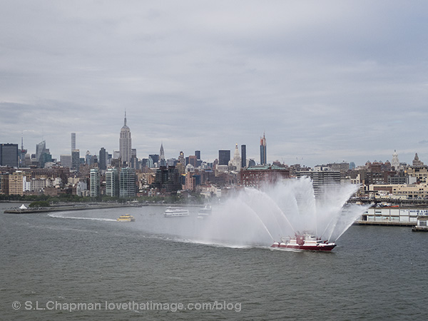 Fireboat in the harbor in NYC. The Empire State Building can be seen in the background. I used to work there, a long time ago!