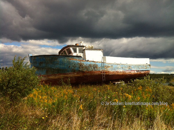 Rusty old boat against a very dramatic sky in the village of village of Marie Joseph in Nova Scotia, Canada