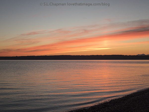 Sunset's brilliant colors reflected in the waters of Puget Sound in Washington State